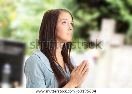 Woman praying next to grave in cemetery - stock photo
