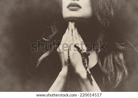 Woman praying with rosary sepia retro vintage - stock photo