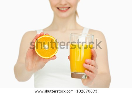 Woman presenting an orange while holding a glass against white background - stock photo
