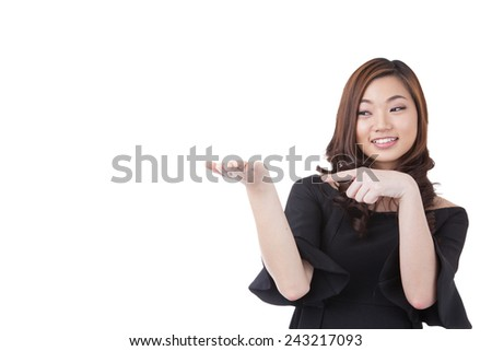 Woman presenting your product in her open hand / palm. Casual beautiful young mixed race chinese / caucasian businesswoman isolated on seamless white background. - stock photo
