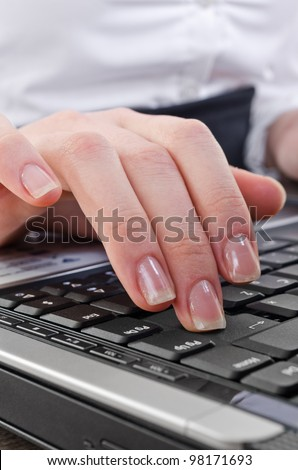 woman pressing enter key on the laptop computer keyboard, selective focus on key-press - stock photo