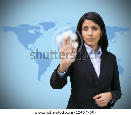 Woman pressing hand to holographic screen against world map - stock photo