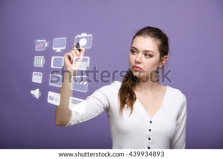 Woman pressing multimedia and entertainment icons on a virtual background - stock photo