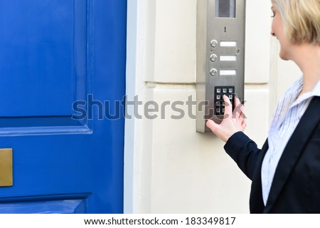 Woman pressing security system buttons - stock photo