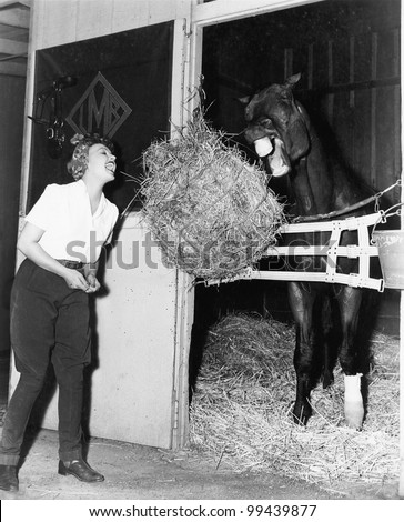 Woman pretending to eat hay bale with horse - stock photo