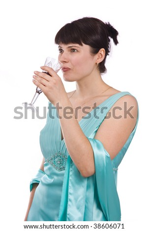 Woman proposes a toast to smb's health. Girl in greenness of the sea dress is standing and holding a glass of wine. - stock photo