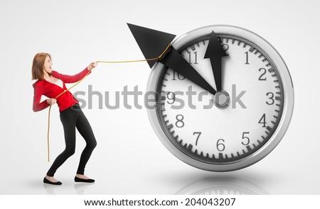 Woman pulling clock hands backwards - stock photo