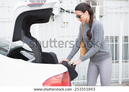 Woman pulling out a baggage of her car trunk in a car park - stock photo
