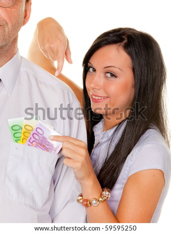Woman pulls a man ? bills from his pocket - stock photo