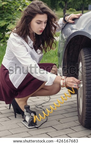 Woman pumps her car tire using a compressor - stock photo