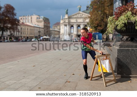 Woman punching at control point, taking part in orienteering city race competitions in old european city. File contains clipping path of woman. - stock photo
