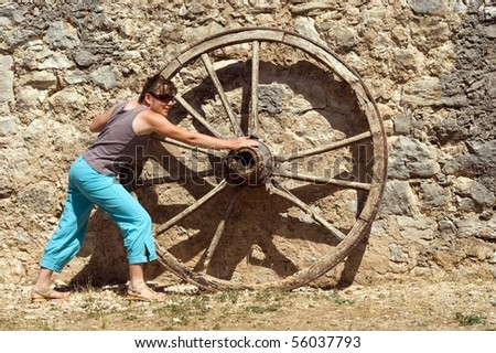 Woman pushed wheel - brickwall background - stock photo