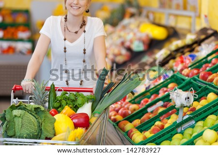 Woman pushing a shopping trolley full of fresh fruit and vegetables through a supermarket for a healthy diet - stock photo