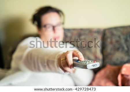 Woman pushing button on remote control.Unrecognizable - stock photo