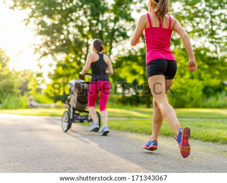 Woman pushing her little girl in a toddler while running outside with friends at sunset - stock photo