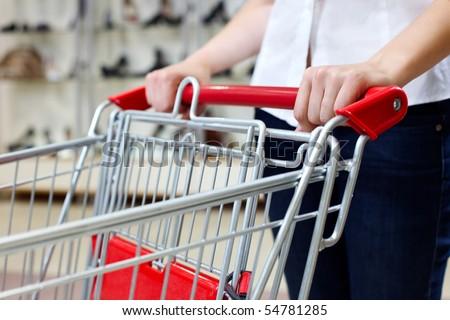 Woman pushing shopping cart in shoe store - stock photo