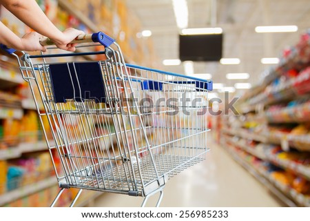 woman pushing shopping cart in supermarket - stock photo