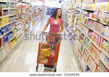 Woman pushing trolley along supermarket grocery aisle - stock photo