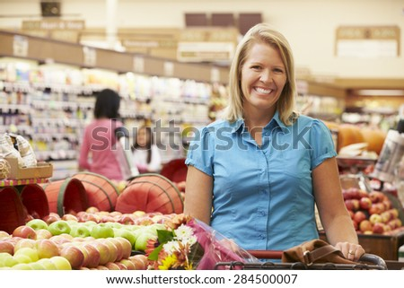 Woman Pushing Trolley By Fruit Counter In Supermarket - stock photo