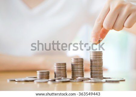 woman put coins to stack of coins - stock photo