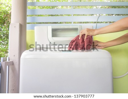 woman putting clothes in washing machine to clean - stock photo
