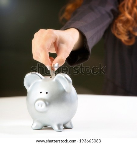 Woman Putting Coin In Piggy Bank. - stock photo