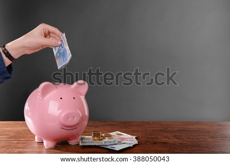 Woman putting euro banknote in pig moneybox - stock photo