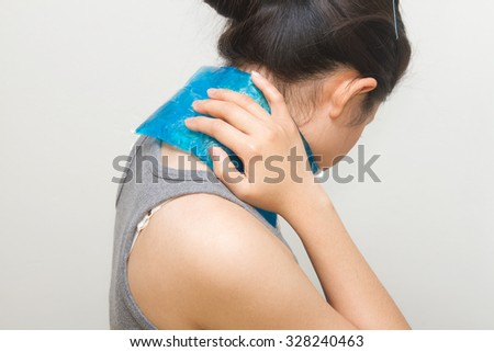 woman putting gel pack on swollen neck - stock photo