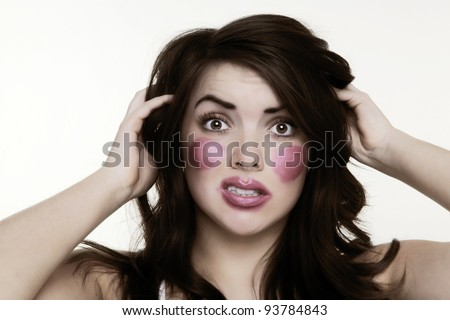 woman putting make up on and it when a bit to far so she looks like its been one by a child. Please note this image has had a half colour and black and white with a sepia toning effect added. - stock photo