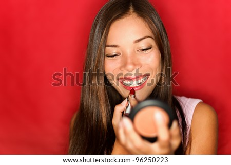 Woman putting makeup lipstick. Asian girl putting lip gloss red lipstick smiling happy looking in pocket mirror. Beautiful young mixed race Asian / Caucasian on red background. - stock photo