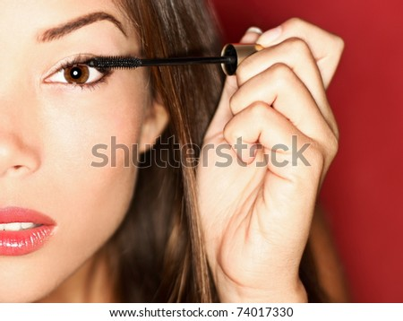 Woman putting mascara makeup. Closeup of gorgeous multi-ethnic Chinese Asian / white Caucasian female model getting ready for a night out. - stock photo