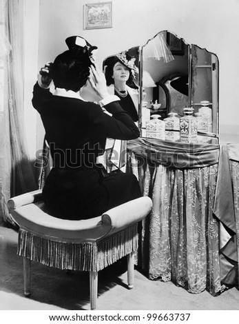 Woman putting on a hat in front of a dressing table - stock photo