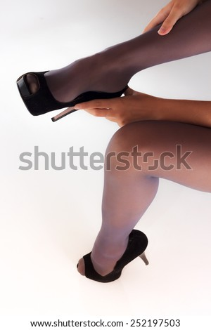Woman putting on her shoes over stockings view 3 - stock photo