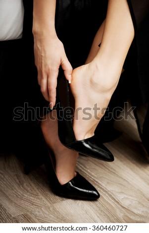 Woman putting on high heels. - stock photo