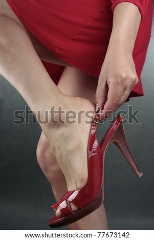 Woman  putting on high heels shoes over grey background - stock photo