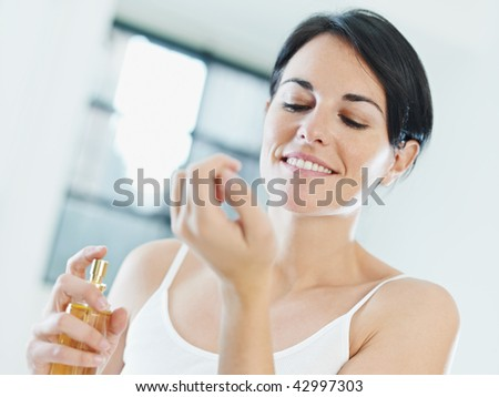 woman putting on perfume and smiling. Copy space - stock photo