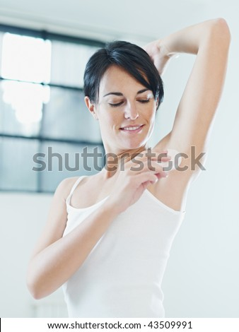 woman putting on stick deodorant and smiling. - stock photo