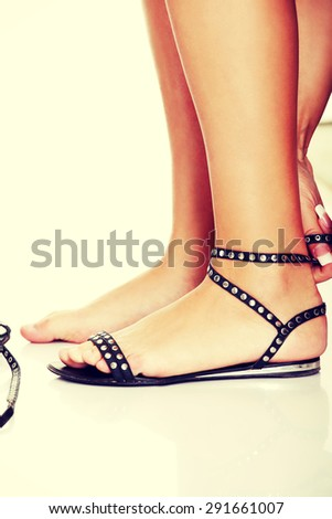Woman putting sandals on her feet - stock photo