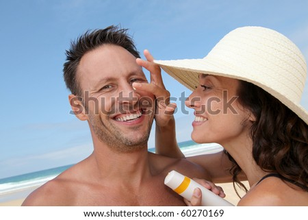 Woman putting sunblock on her boyfriend's nose - stock photo