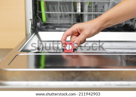 Woman putting tablet in dishwasher detergent box - stock photo