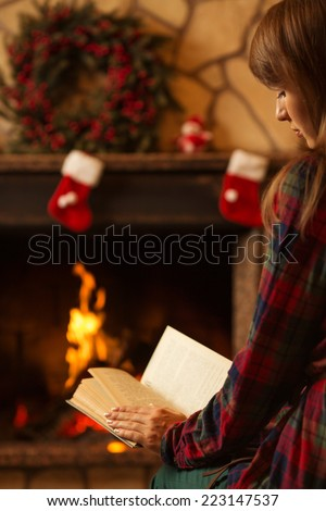 Woman reading a book by the fireplace. Young woman reading a book by the warm fireplace decorated for Christmas. Relaxed holiday evening concept.  - stock photo
