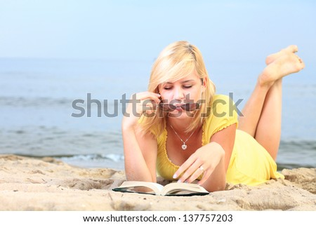 woman reading a book girl the yellow dress water beach - stock photo