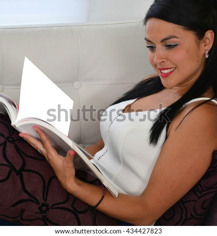 Woman reading a book relaxing at home. - stock photo