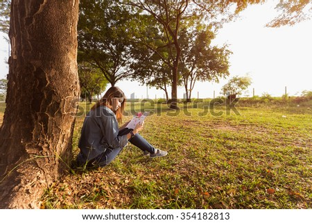 Woman reading a book under the tree. - stock photo