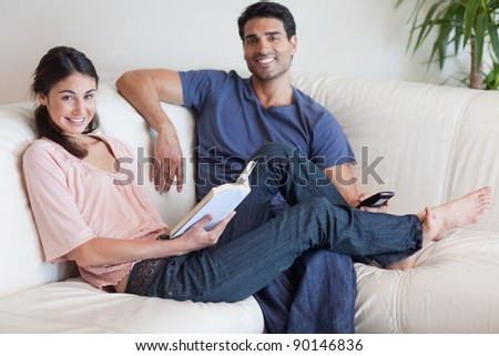 Woman reading a book while her husband is watching TV in their living room - stock photo