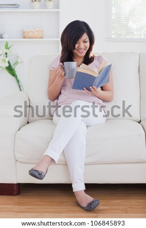 Woman reading a book while sitting on a couch in a living room - stock photo