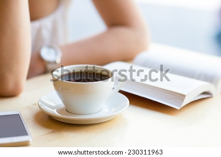 Woman reading book and drinking coffee at cafe - stock photo