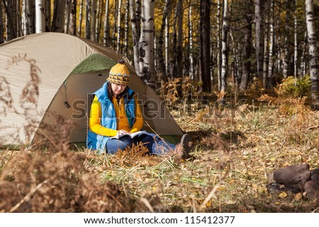 Woman Reading Book at Campsite - stock photo