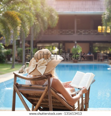 woman reading book in deck chair near swimming pool - stock photo