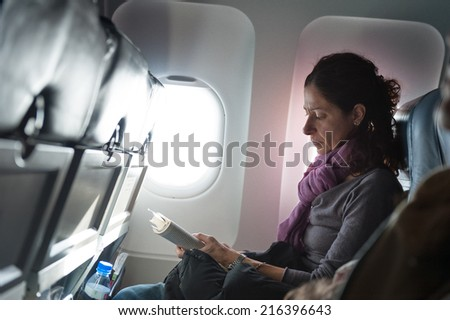 Woman reading book inside airplane. - stock photo